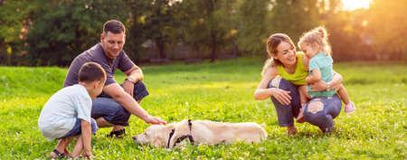 gelukkige familie heeft plezier met golden retriever - spelen met hond in park en gelukkige familie