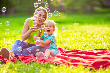 Happy family in park -Cute female child blows soup foam and make bubbles with her mother in nature