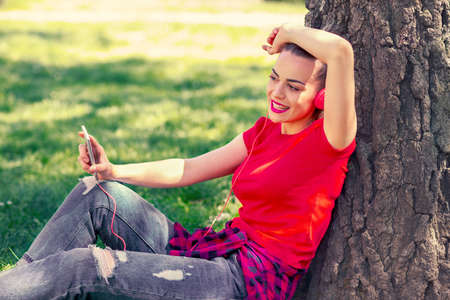 Play music - cool woman with headphones listening to music in park Stock Photo