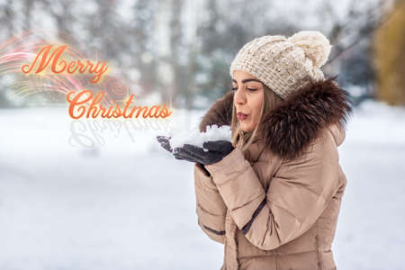 beautiful young girl blowing magic snow Marry Christmas