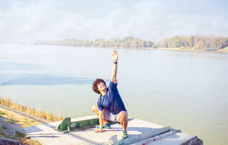 Man performing yoga – young man outdoor doing exercise 免版税图像
