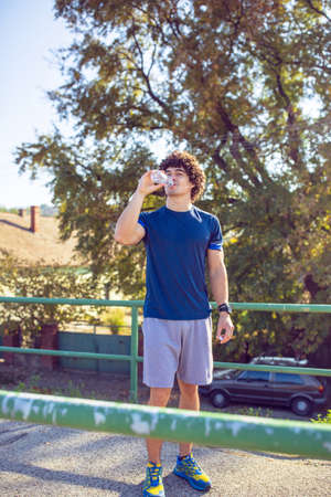 fitness, sport, training and lifestyle concept -Young man drinking water 免版税图像