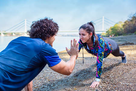 fitness couple giving high five to each other while doing push up together outdoors