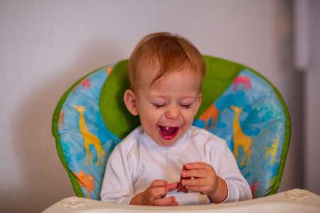 Happy adorable baby boy eating delicious chocolate