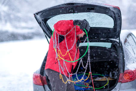 Young man prepares chains for tires on a cold day