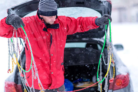 young man with gloves install snow chains in the car tyre in winter on snow