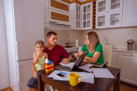 Family budget and finances- young man and woman with daughter planning home budget