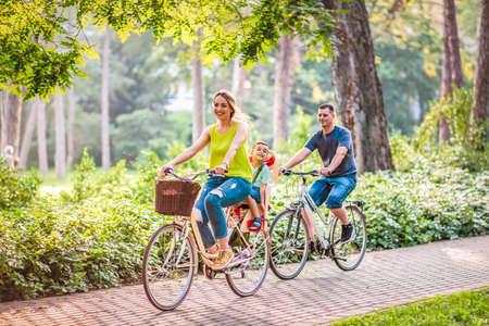 Glückliche Familie fährt draußen Fahrrad und lächelt Standard-Bild