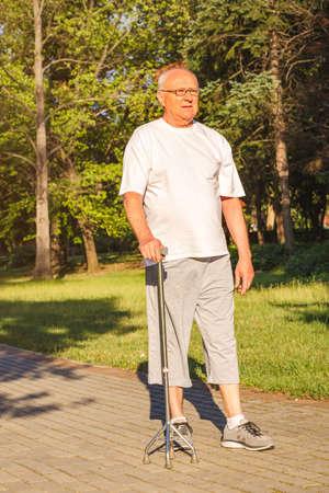 Sonriente hombre senior disfrutando de caminar en el parque con bastón Foto de archivo