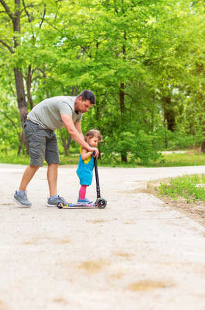 father teaching his cute little daughter to ride kid scooter at the park