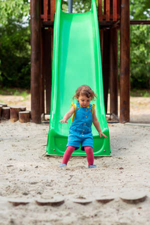 Happy childhood - little girl chuting down slide at playground