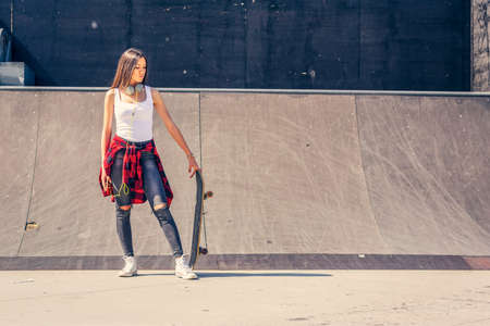 Young girl skateboarder in skateboard park