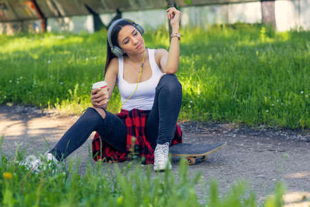Sporty cool skateboarder girl sitting on skateboard drink coffee and listing music Stock Photo