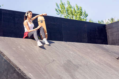 Cute teen girl with skateboard listening music in skate park.
