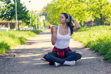 Cool skateboarder girl sitting on skateboard and drink coffee
