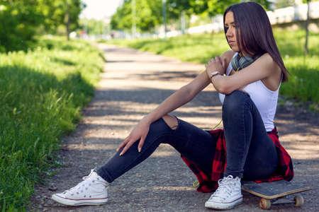 Sporty girl sitting on skateboard on street. Outdoors, urban lifestyle.