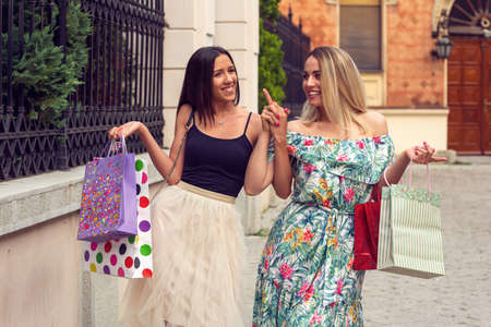 Happiness, friends, sale and fun concept-smiling young girlfriends with shopping bags. Stockfoto