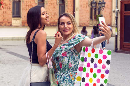 Two beautiful women in buying on the shopping day and take selfie with mobile phone