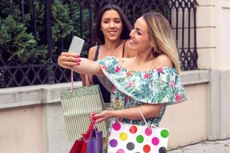 Two beautiful girl in buying on the shopping day and take selfie with mobile phone