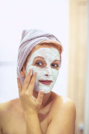 cream on her face, mask on the face, problem skin - Woman applying facial mask. Stockfoto
