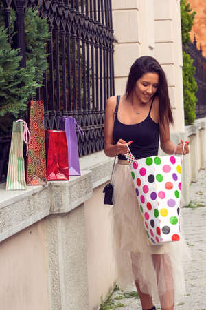 smiling woman with shopping bags bought clothes and shoes