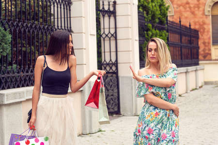 two young girl arguing at shopping in the city.