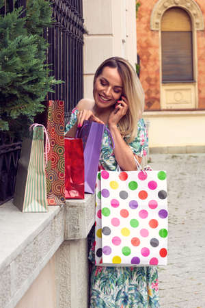 Beautiful smiling woman holding shopping bags, using a smart phone and smiling while standing outdoors