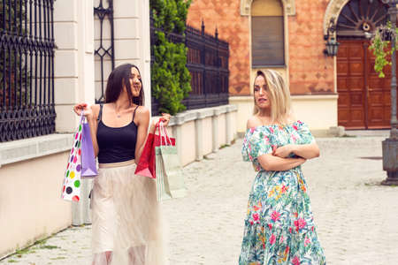 Sad and happy woman arguing at shopping in the city. Stockfoto
