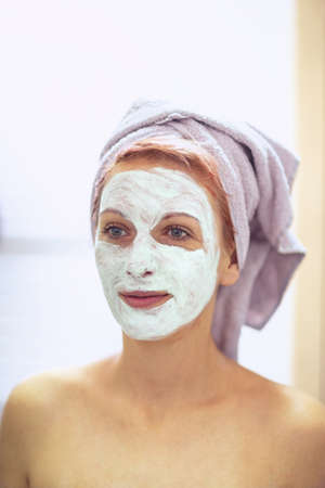 Beautiful young woman with facial mask - cream on her face, mask on the face, problem skin