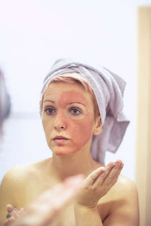 Young woman with a facial mask - Skincare and cosmetics concept.