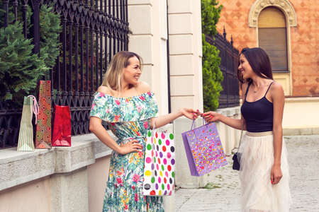 Smiling shopping girls in the street with bags