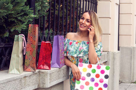 Beautiful woman holding shopping bags, using a smart phone and smiling while standing outdoors Stockfoto
