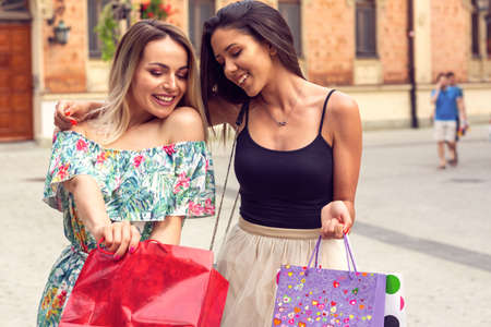 Happiness, friends, sale and fun concept - Young girls with shopping bags in the city.