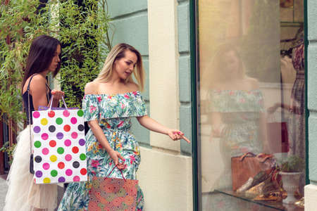 Two young women in shopping looking at shop window in the city Stockfoto