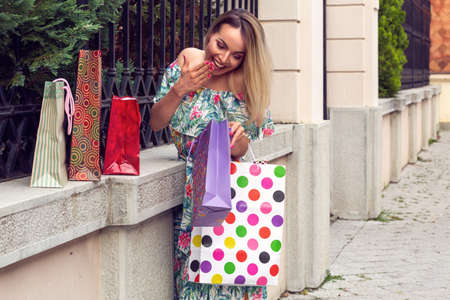 Happy shopping – young woman holding shopping bags and smiling while standing outdoors Stockfoto
