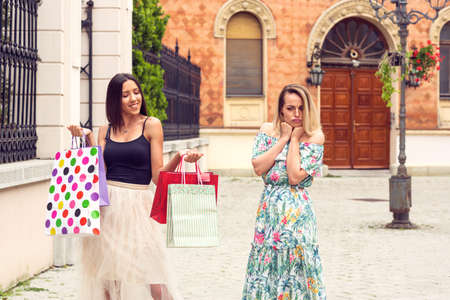 Sad and happy women at shopping in the city. Stockfoto