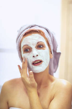 cream on her face, mask on the face, problem skin – Smiling woman with a face mask.