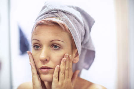 Young woman is worried about the wrinkles on her face. Skin care concept.