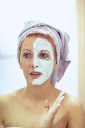 Young smiling woman applying facial mask. Beauty treatments.