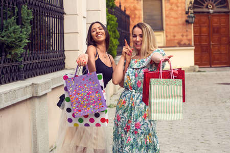 smiling young girlfriends with shopping bags.