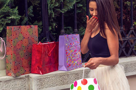 shopping bags – happy woman holding shopping bags and smiling while standing outdoors
