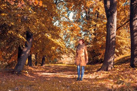 Beautiful woman walking outdoors in autumn park.