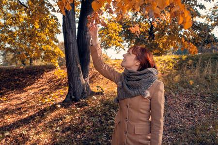 Cheerful young redhead woman enjoying in park Stockfoto