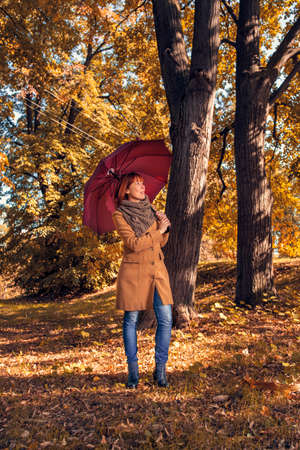 Fun in the autumn forest -Young woman with red umbrella walking on autumn park
