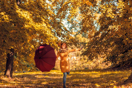 Fun in the autumn forest - Smiling redhead girl with umbrella enjoying in nature Stockfoto