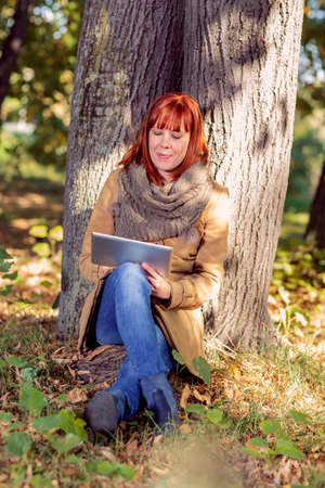 Young woman sitting under a tree in autumn park with tablet
