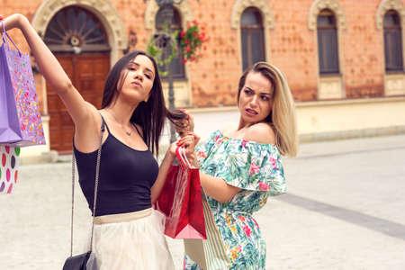 mujeres de compras. dos mujeres jóvenes discutiendo en compras en la ciudad.