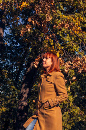 Colorful foliage in the park. Falling leaves natural background. Happy young red hair woman in nature