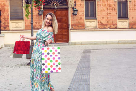 Beautiful shopaholic girl happy holding shopping bags.