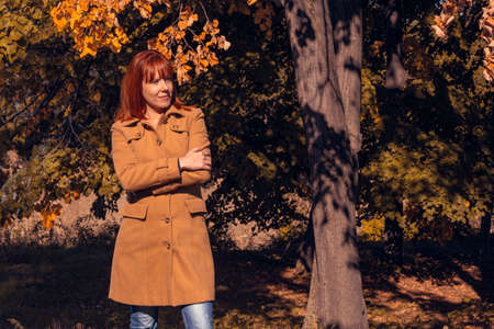 sunny autumn park. cheerful Cute ginger girl in nature  Imagens